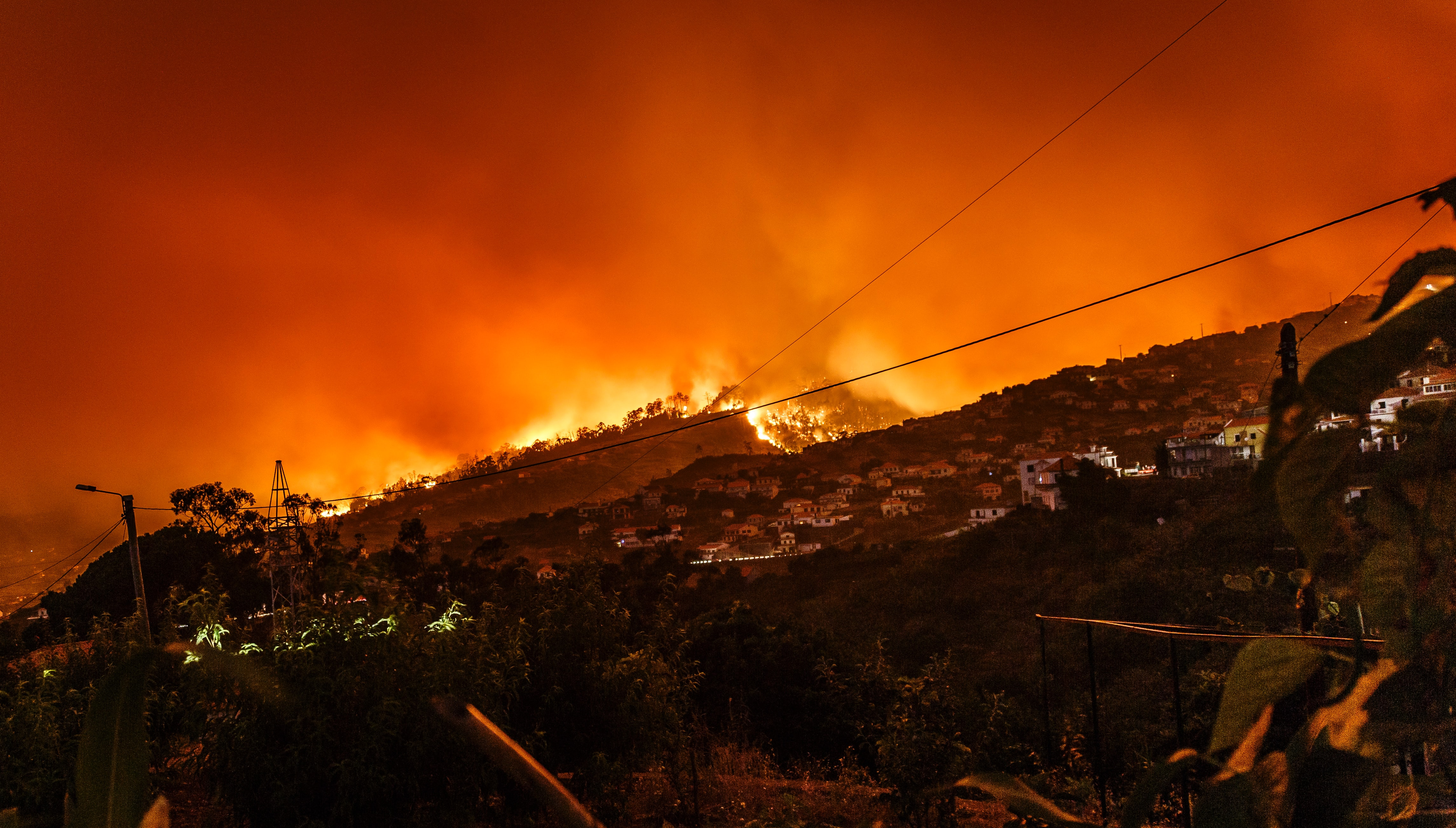 Image of a wildfire encroaching on a town in Portugal.