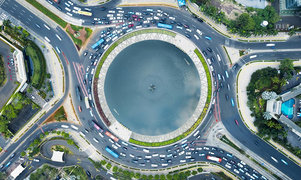 JAKARTA, Indonesia - December 17, 2019: Tilted top down horizontal view of a fountain in the middle of a roundabout in Jakarta city at sunny morning.
